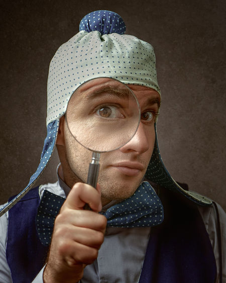 Portrait of man holding magnifying glass