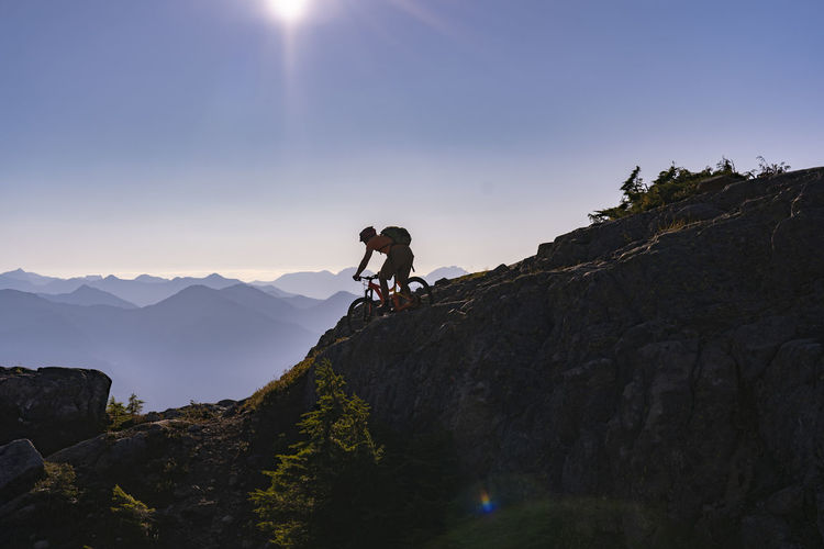 Hiker riding bicycle on mountain against sky