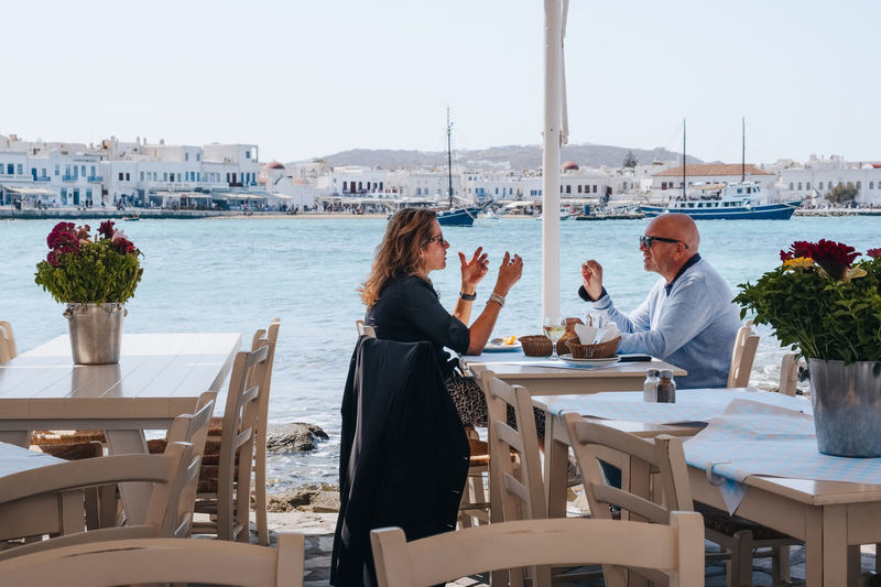 People sitting at restaurant by sea against sky