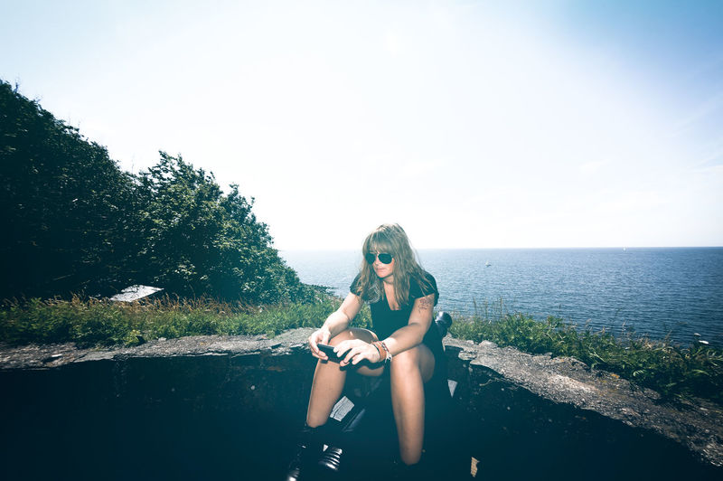 Young woman using mobile phone while sitting on retaining wall against sea