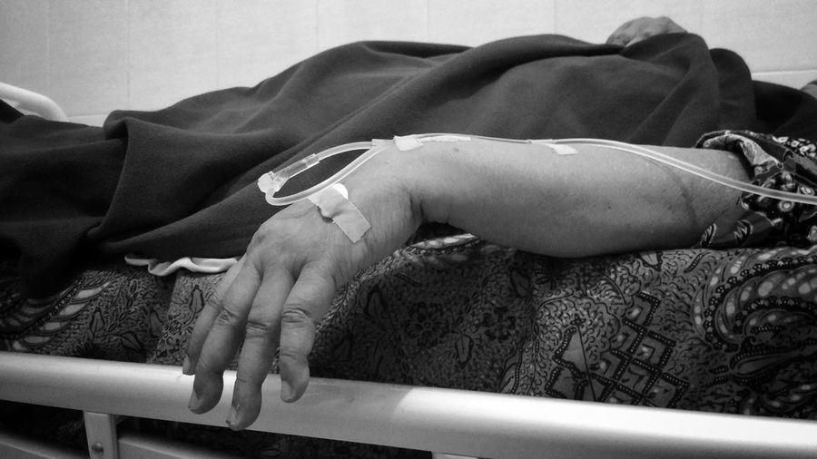 Midsection Of Woman Sleeping On Bed In Hospital