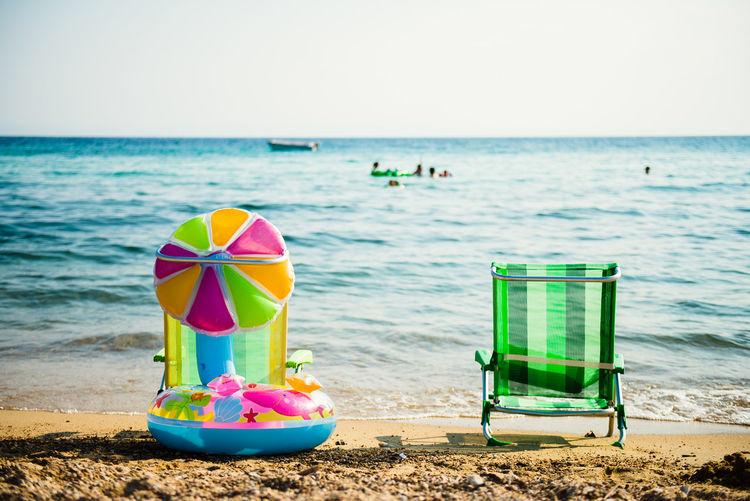 Deck chairs on beach against clear sky
