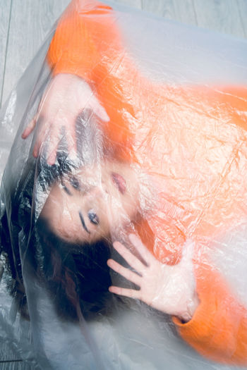 Portrait of teenage girl wrapped in plastic on floor