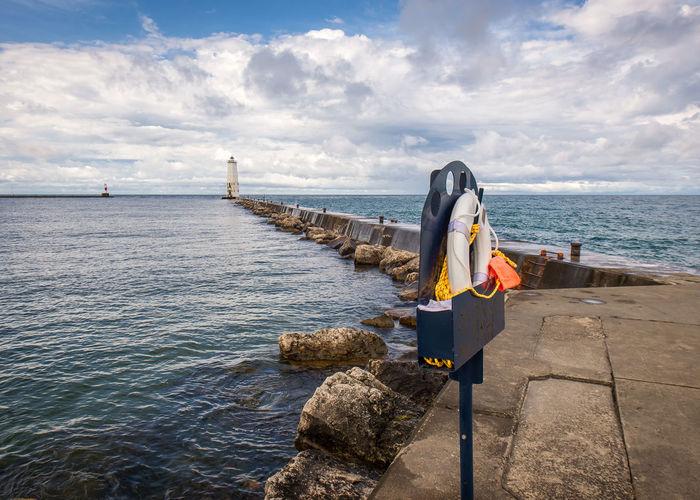 Life belt on groyne in sea against sky