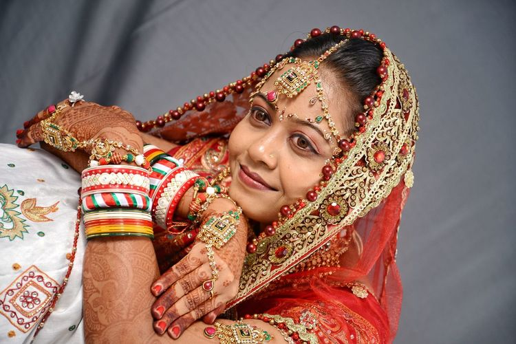 Close-up of beautiful young bride against curtain
