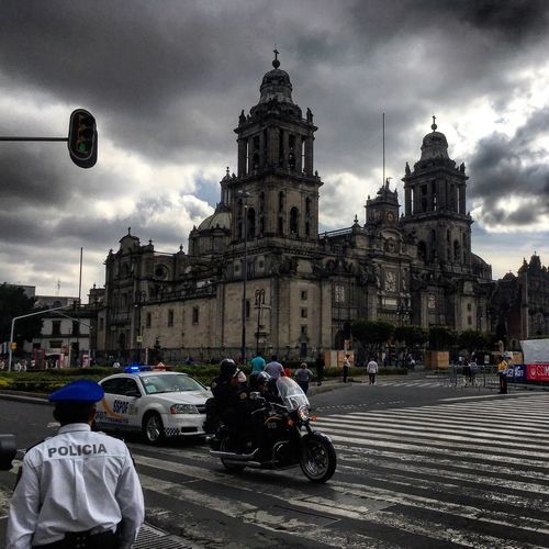 Road passing through city against cloudy sky