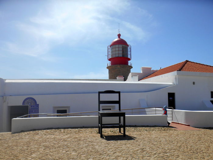 View of lighthouse by building against sky