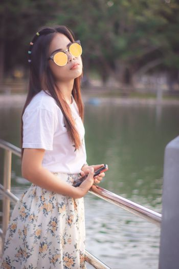 Portrait of woman in sunglasses standing against lake