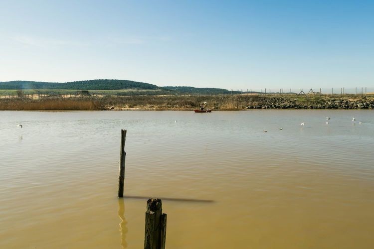 Wooden posts in river against sky on sunny day