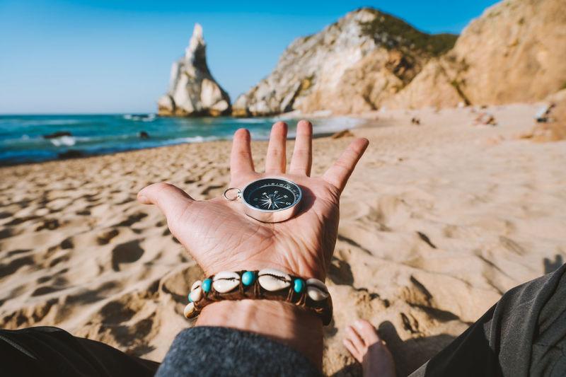 Close-up of hand holding navigational compass at beach