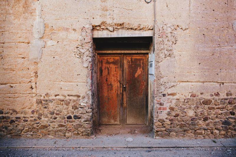 Door of an old adobe house in the village llamas de la ribera, rural león. spain