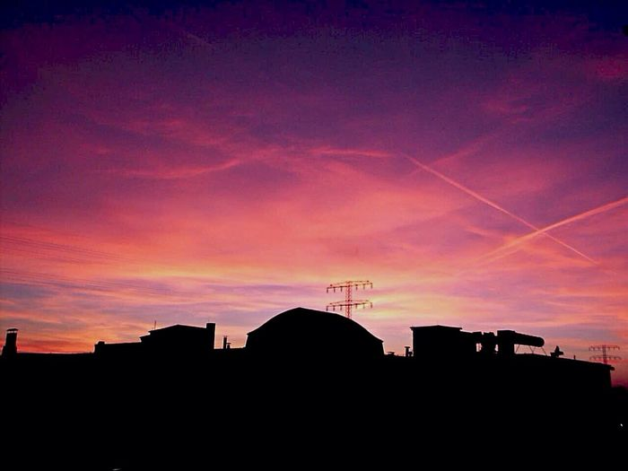 Low angle view of silhouette buildings against sky at sunset
