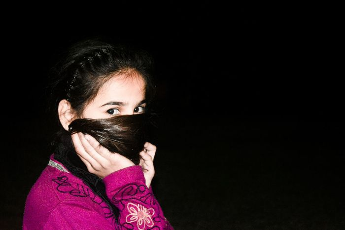 Girl covers her face with hair.