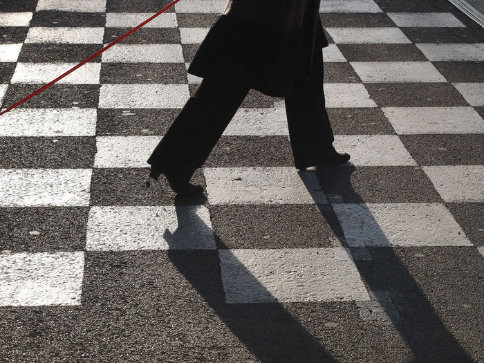 Low section of woman walking on checked patterned road
