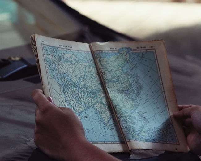 Cropped Hands Holding Map Book