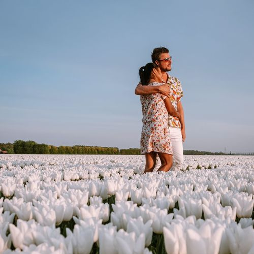 Couple embracing amidst white flowers against sky