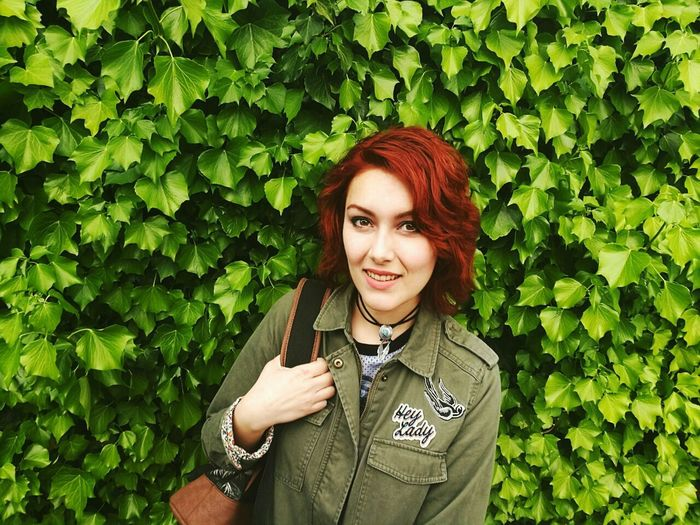 Portrait of redhead woman standing against green creeper plants