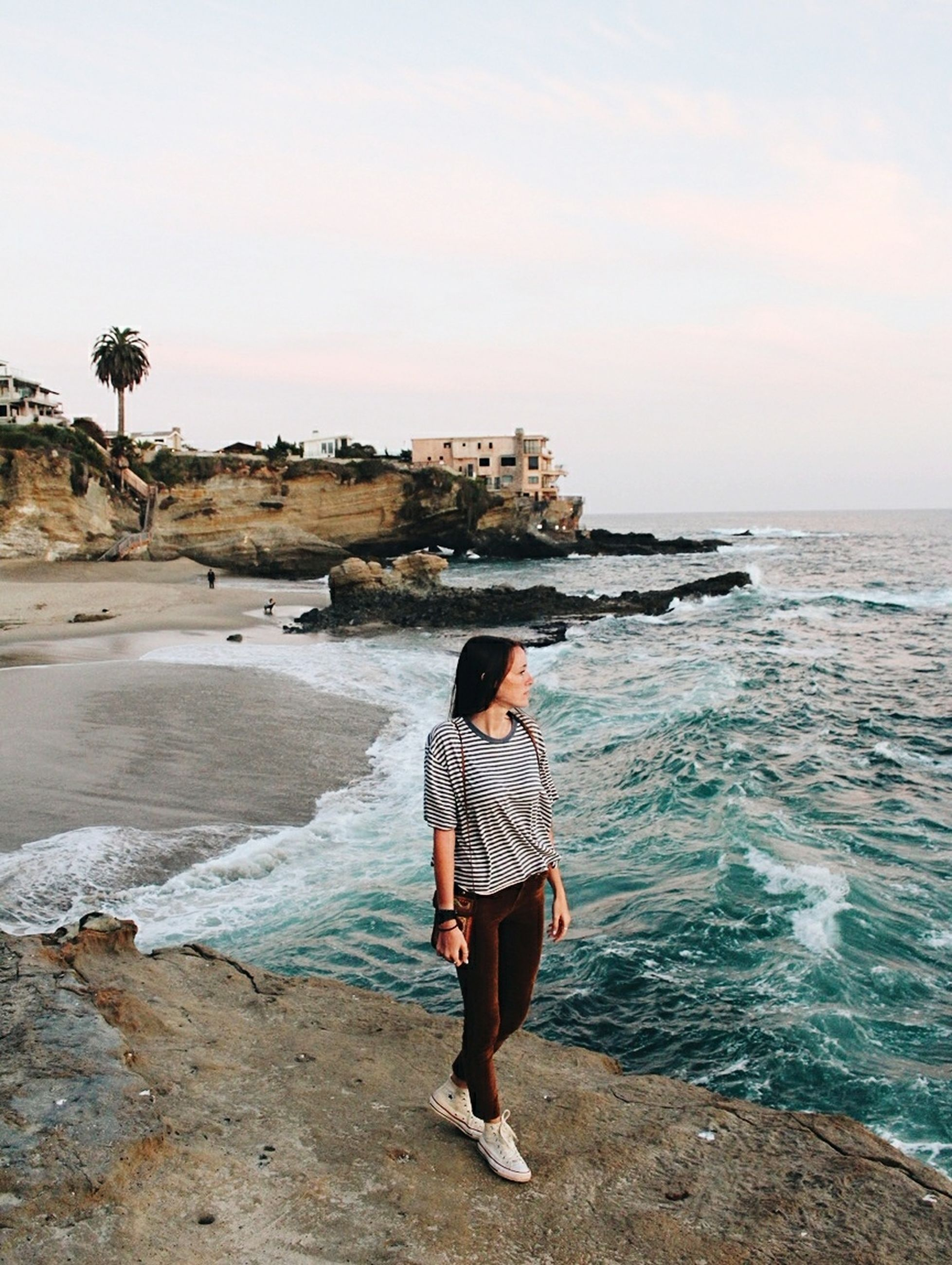 water, sea, real people, lifestyles, sky, one person, beach, leisure activity, land, rock, rock - object, solid, beauty in nature, scenics - nature, standing, casual clothing, young adult, nature, outdoors, looking at view