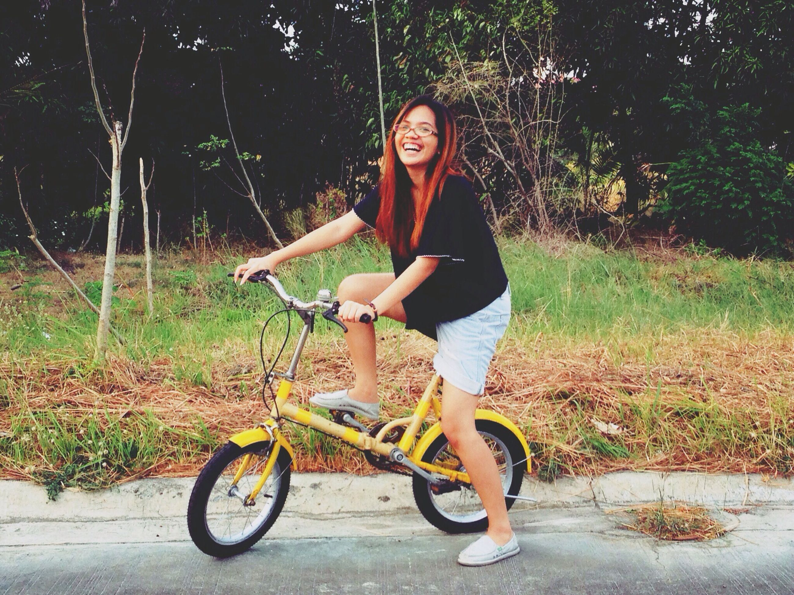 young adult, full length, casual clothing, person, lifestyles, tree, front view, leisure activity, young women, looking at camera, standing, portrait, outdoors, bicycle, plant, holding, smiling, leaning