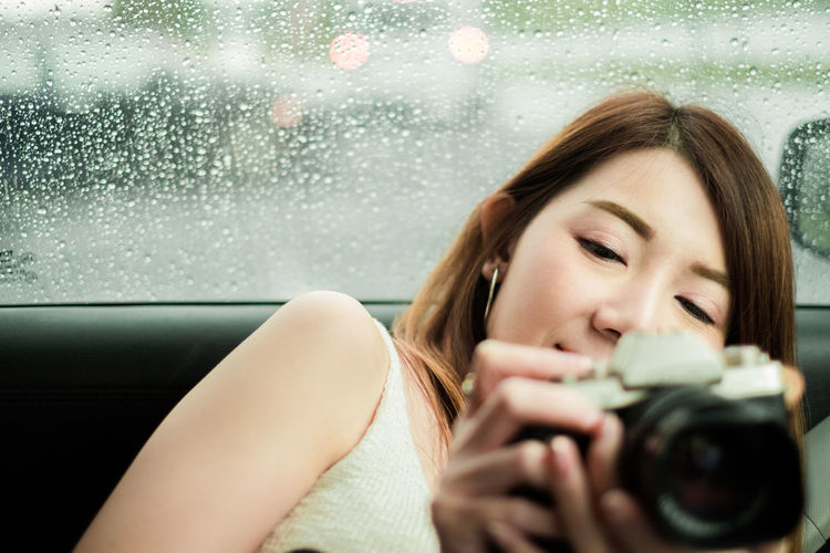 Portrait of smiling woman photographing through window in rain