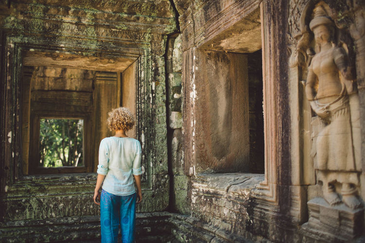Siem Reap Cambodia Angkor Curly Hair Girl One Person Standing Architecture Three Quarter Length Casual Clothing Rear View Day Adult History Women Young Adult Indoors  Architectural Column The Past Built Structure Building Leisure Activity Hairstyle