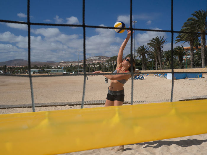 Athletic woman hits the volleyball on the beach Fitness, Activity Attack, Attaktive, Ball Beach Beach Volleyball Beachball Beautiful Bump Dig Female, Hit Jump Matches Net Outdoor Outdoors Play Recreation, Smash  Sport Sportswear, Volleyball Woman