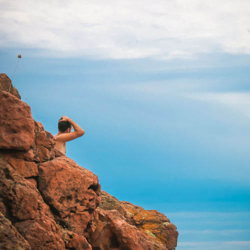 Side view of shirtless man on rock by sea against sky