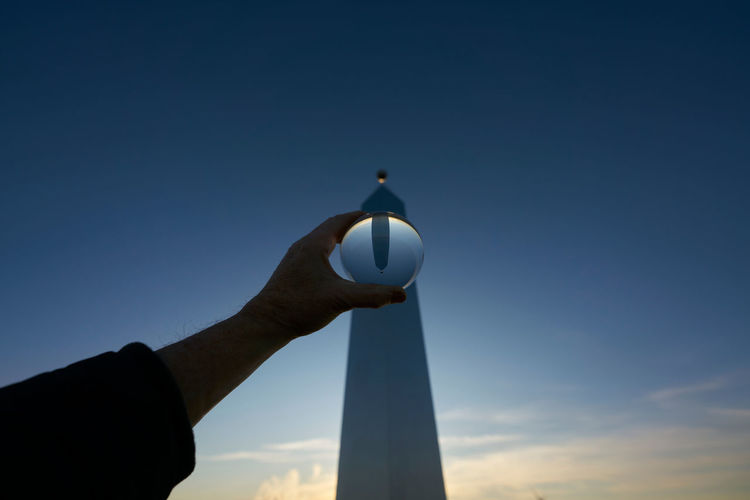 Low angle view of hand holding lighthouse against sky during sunset