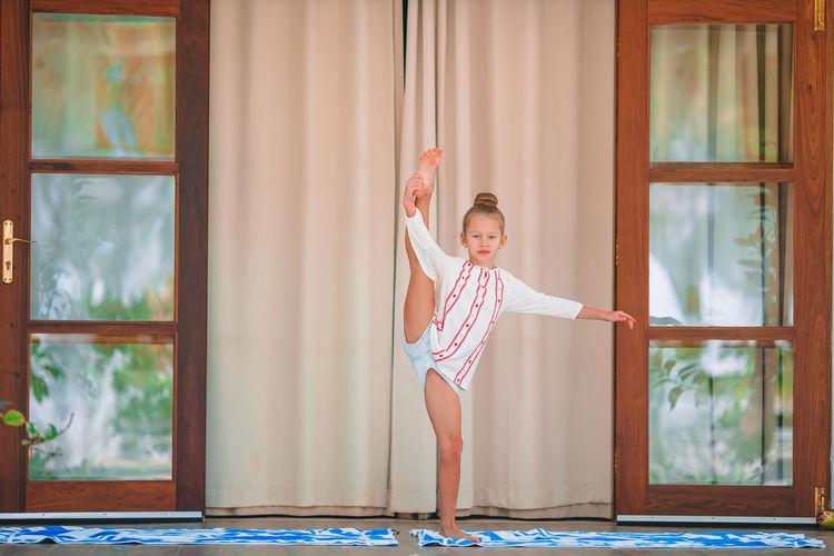 Full length of girl exercising while standing against window