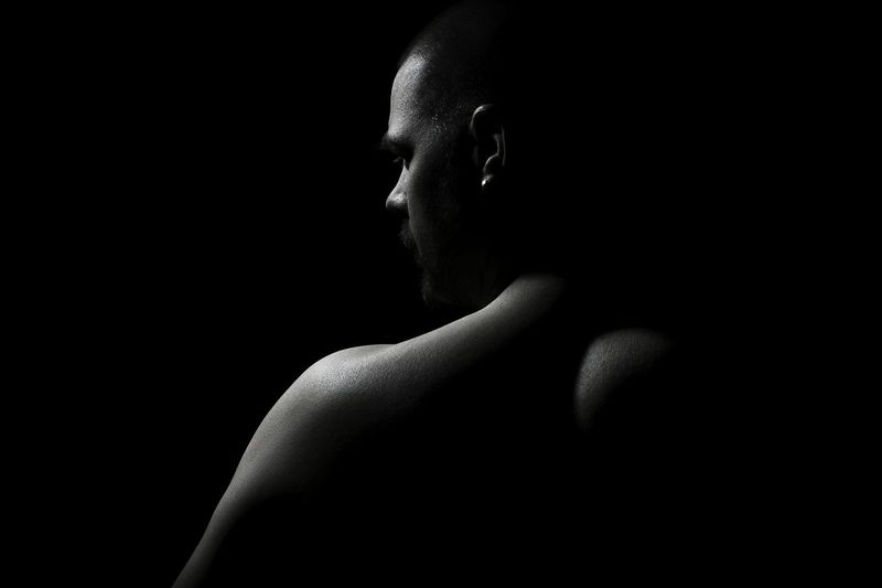 Rear view of shirtless man against black background
