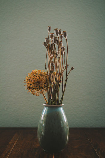 Close-up of vase on table against wall