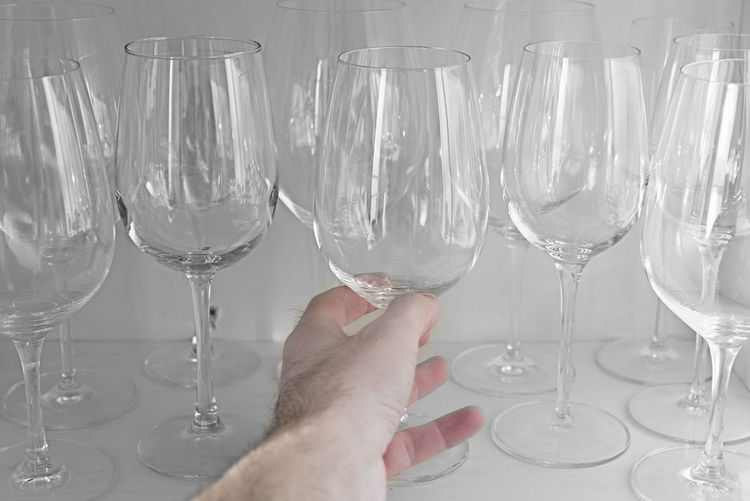 Cropped Hand Of Men Holding Empty Wineglass At Table