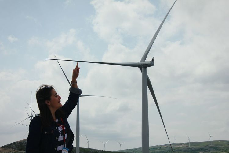 Optical Illusion Of Young Woman Touching Windmill Against Cloudy Sky