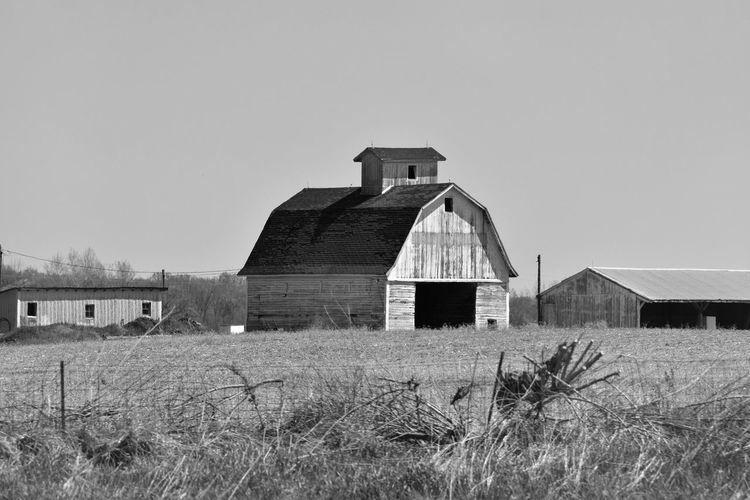 Abandoned barn on field against clear sky