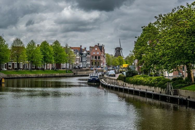 Canal Passing Through City Against Cloudy Sky