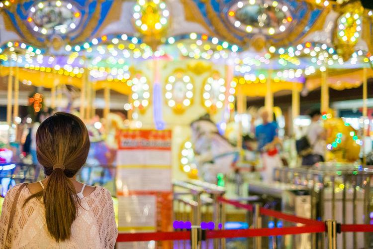 Rear view of woman looking at illuminated carousel at night