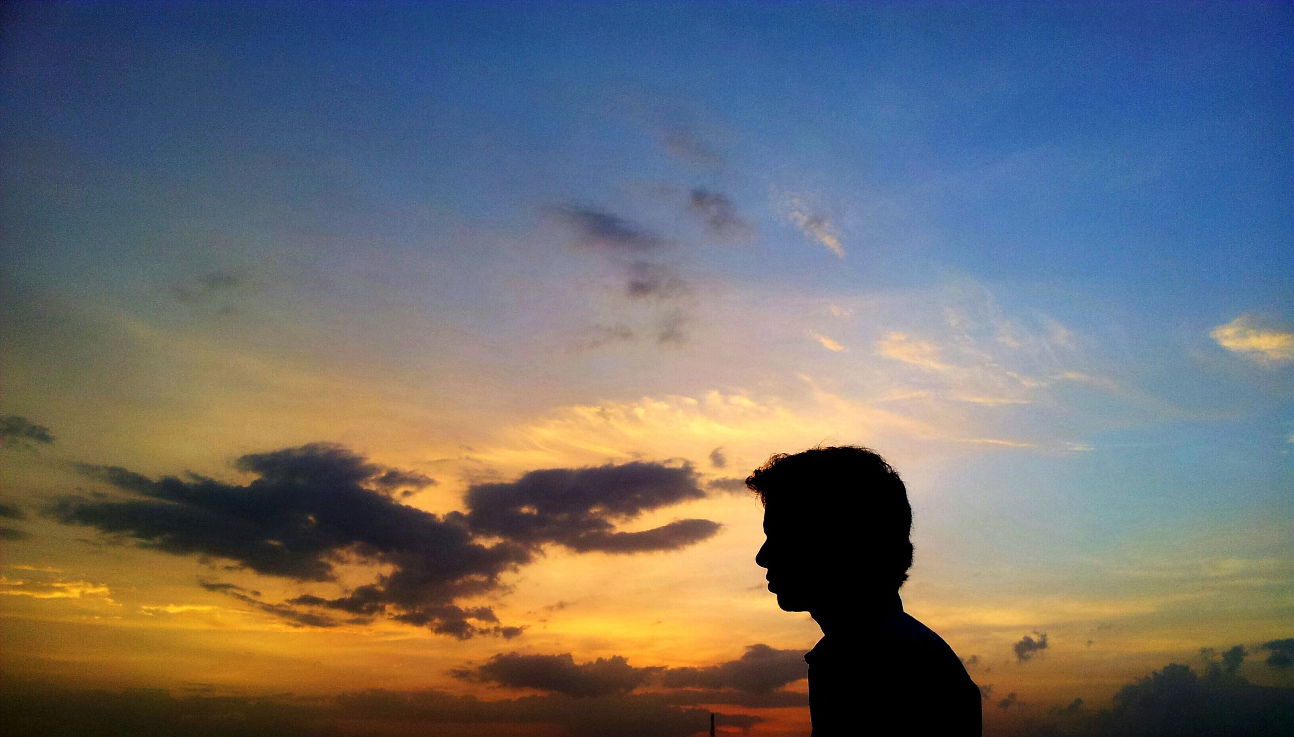 sunset, silhouette, leisure activity, lifestyles, sky, orange color, cloud - sky, nature, beauty in nature, scenics, cloud, field, outdoors, atmospheric mood, tranquility, atmosphere, moody sky, tranquil scene, sun, enjoying