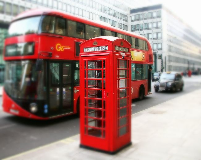 Red telephone booth on road in city
