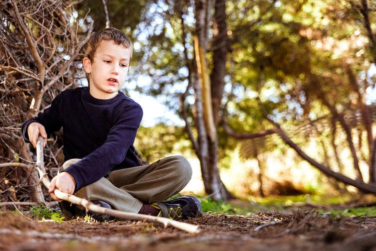 Surface level shot of boy holding stick sitting on ground