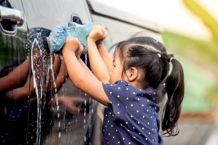 Side View Of Girl Cleaning Car
