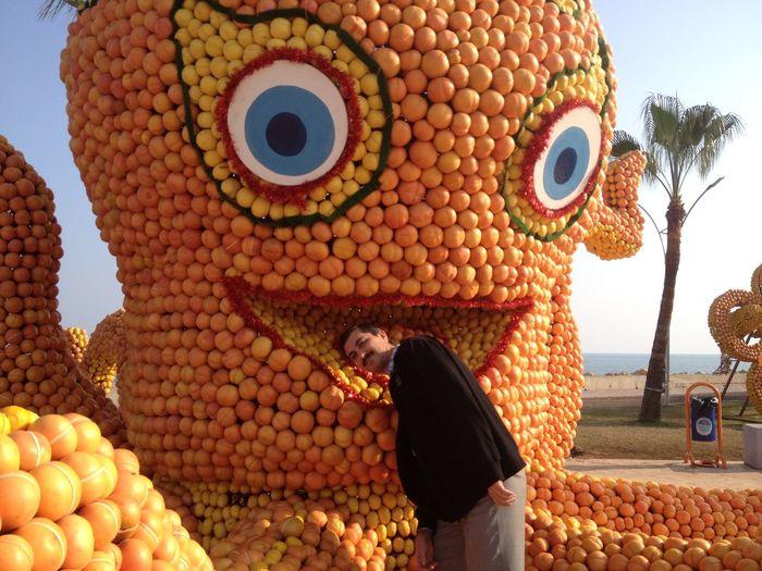 Portrait of man leaning against pumpkin sculpture