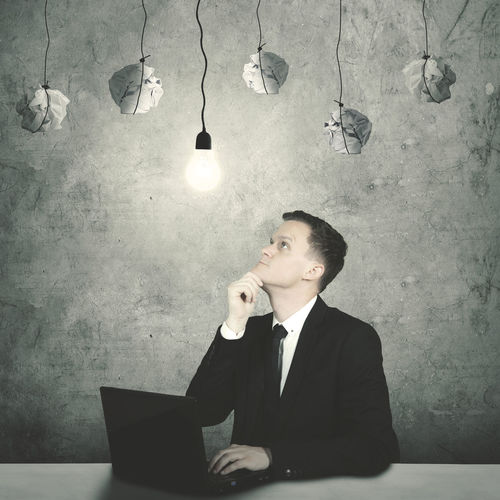 Thoughtful businessman using laptop at desk against wall