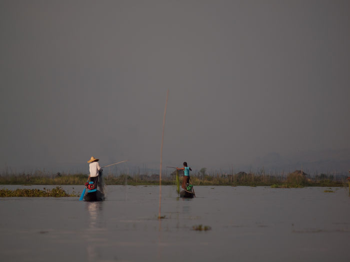 Mid distance view of fishermen fishing in lake