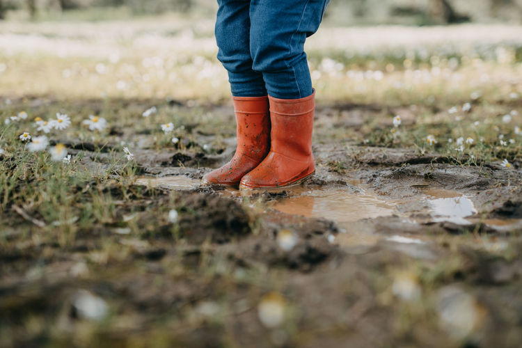 Low section of child standing in puddle with red rubber boots