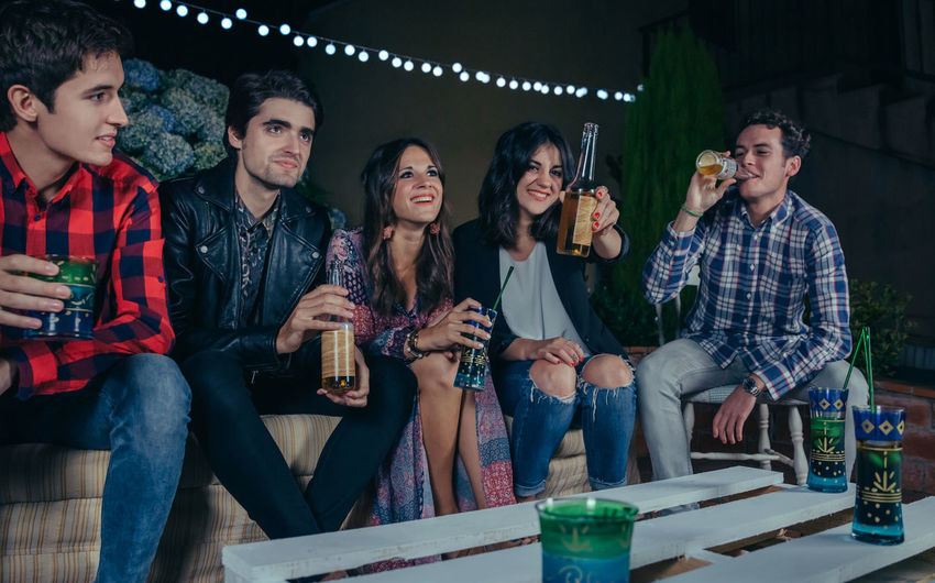 Happy young friends laughing and talking while woman showing beer at camera in a outdoors party. Friendship and celebrations concept. Beer Celebration Friends Fun Happiness Happy Horizontal Millenials Young Alcohol Bottle Cheerful Drink Drinking Entertainment Five People Friendship Group Group Of People Night Nightlife Outdoors Party People Sofa