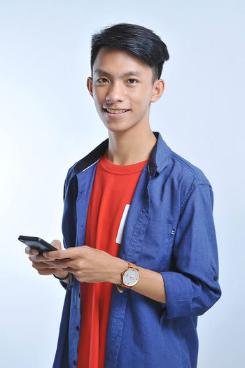 Portrait of smiling man holding smart phone