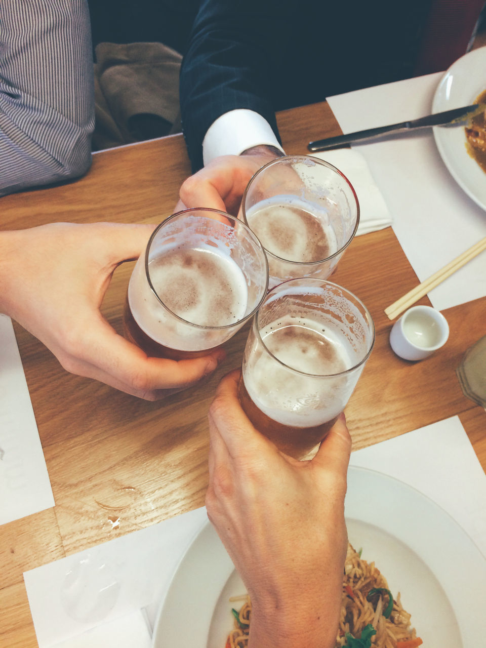 High Angle View Of Men Toasting Beer At Table