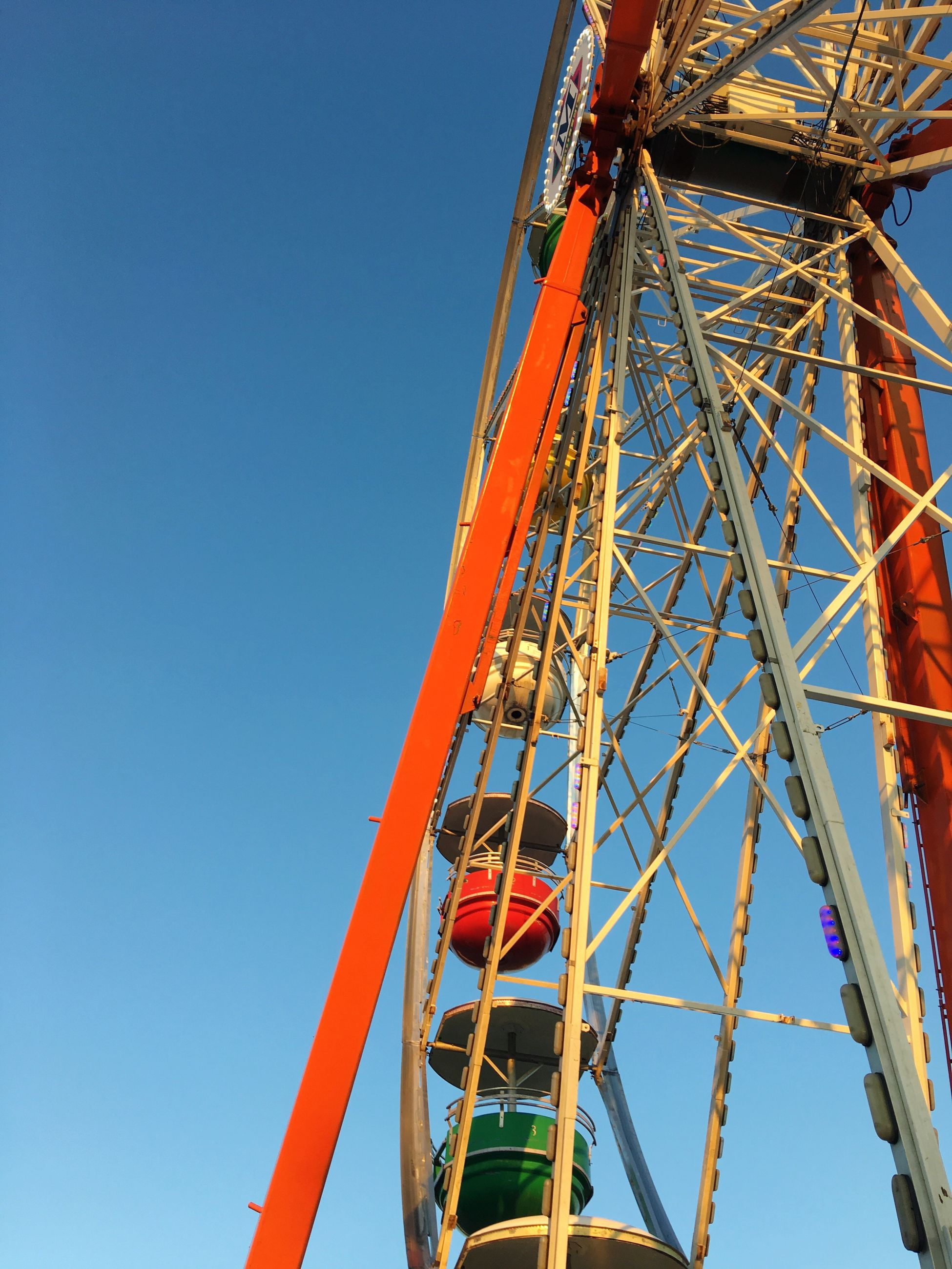 arts culture and entertainment, amusement park, low angle view, amusement park ride, blue, day, clear sky, ferris wheel, no people, outdoors, childhood, sky