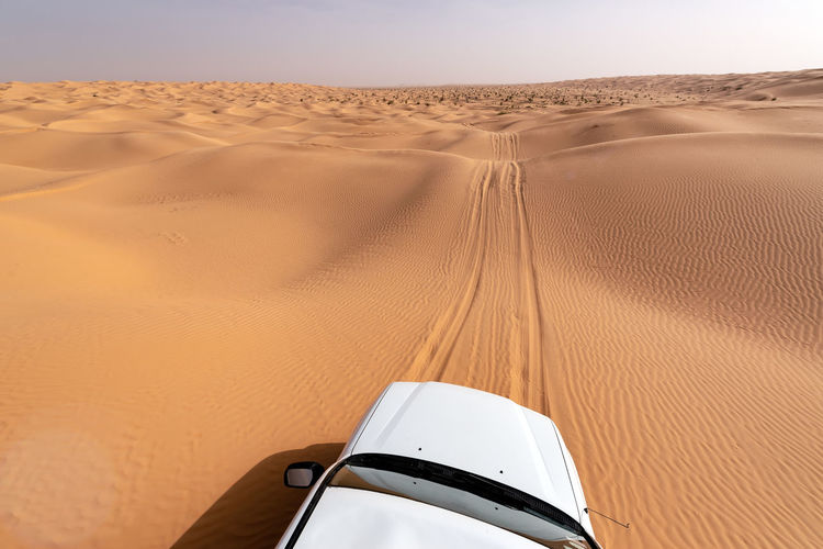 View of the Sahara Desert from the roof of a white SUV in Tunisia Arabian Douz Dunes Extreme Hot Nature SUV Travel Tunisia Above Africa Background Car Desert Dune Land Landscape Nature Sahara Sand Sand Dune Sun Texture Tourism Transportation