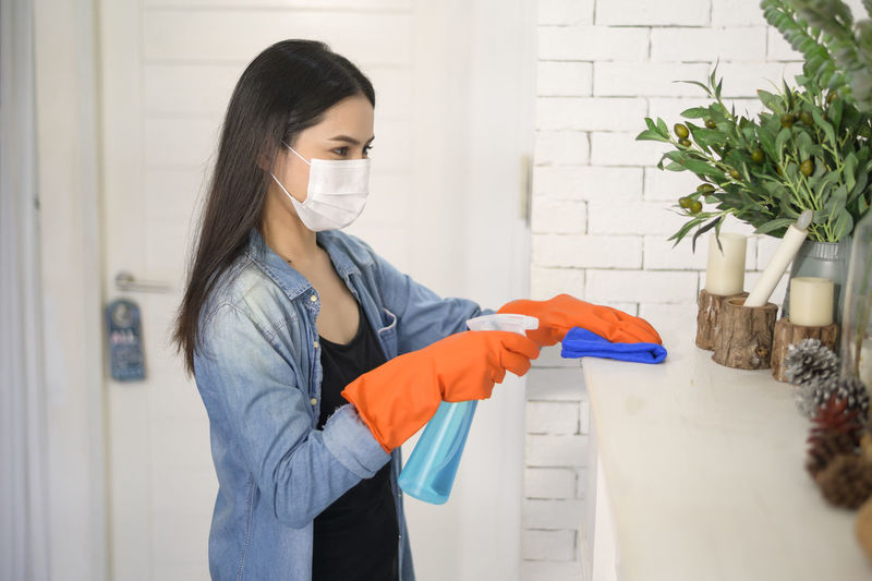 Woman wearing mask cleaning furniture at home